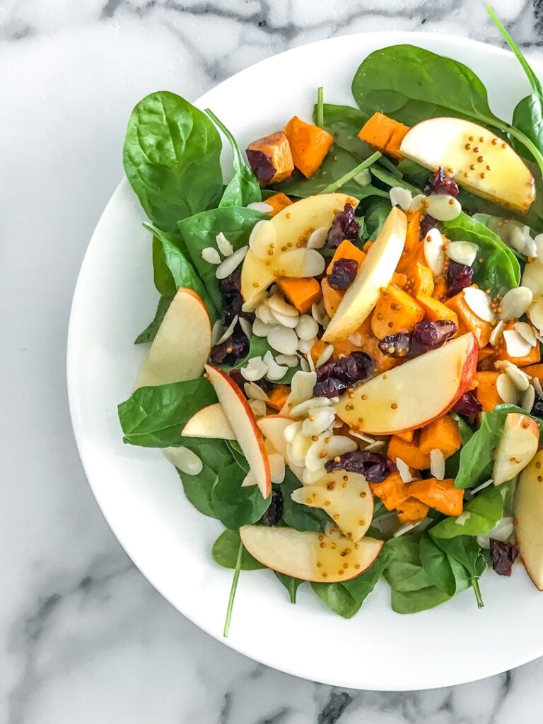 white plate with spinach salad topped with apples, cranberries, almonds, and sweet potatoes