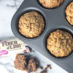 top down view of muffins in muffin tin with fiber bar and crumbs on counter