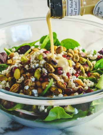 Crisp Winter Salad with Pomegranate and Pistachios dressing pour