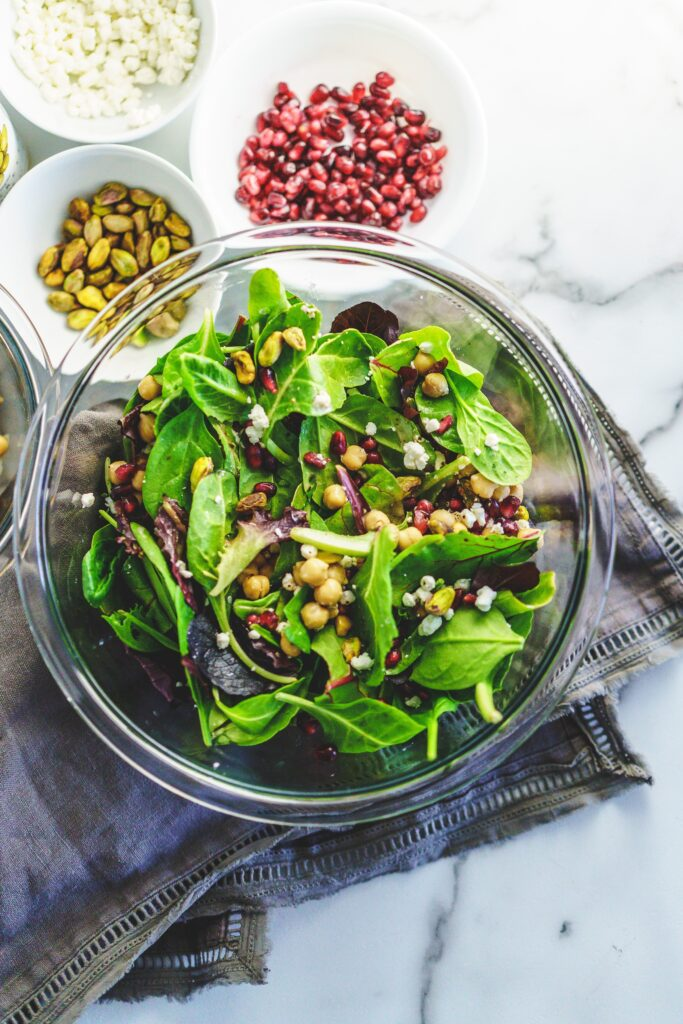 clear bowl of mixed greens topped with chickpeas, pistachios, goat cheese, and pomegranate arils