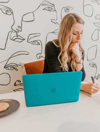 woman on laptop writing in notebook