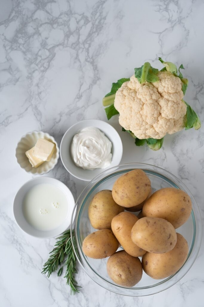 head of cauliflower and bowls with potatoes, sour cream, milk, and butter against marble background