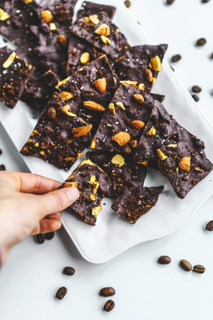 hand grabbing chocolate piece with almonds