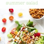 plate with salad topped with chickpeas vegetables and ranch dressing