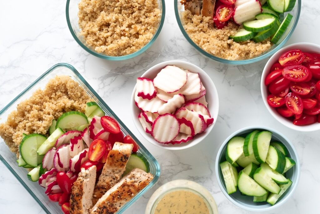 rectangular food container with quinoa, chicken and vegetables and circular prep bowls with ingredients
