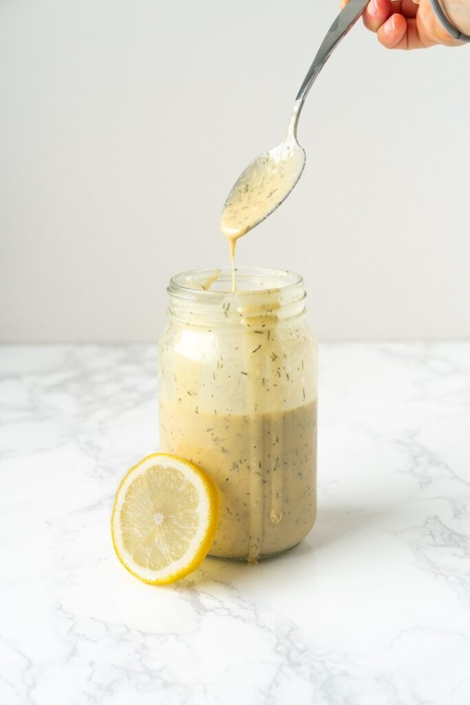 jar with creamy dressing, lemon slice, and a dripping spoon