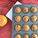 muffin tin filled with baked apple pumpkin muffins