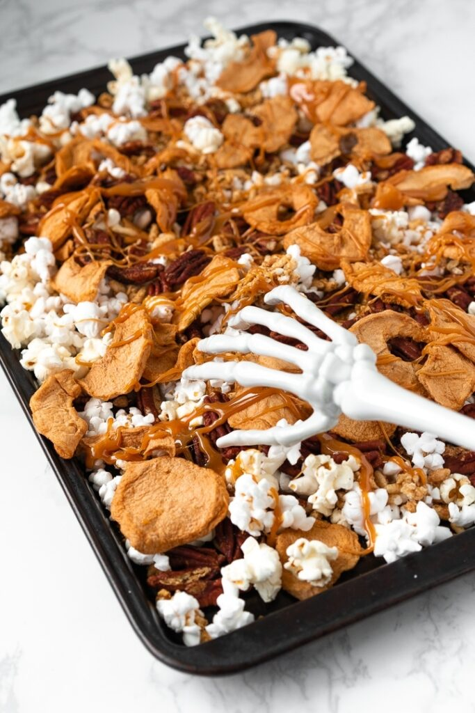 skeleton hand reaching for baking sheet covered with halloween trail mix