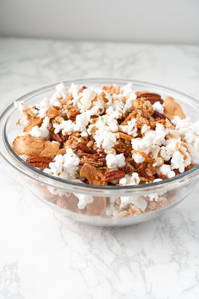 clear bowl with popcorn, pecans, dried apples, and cereal