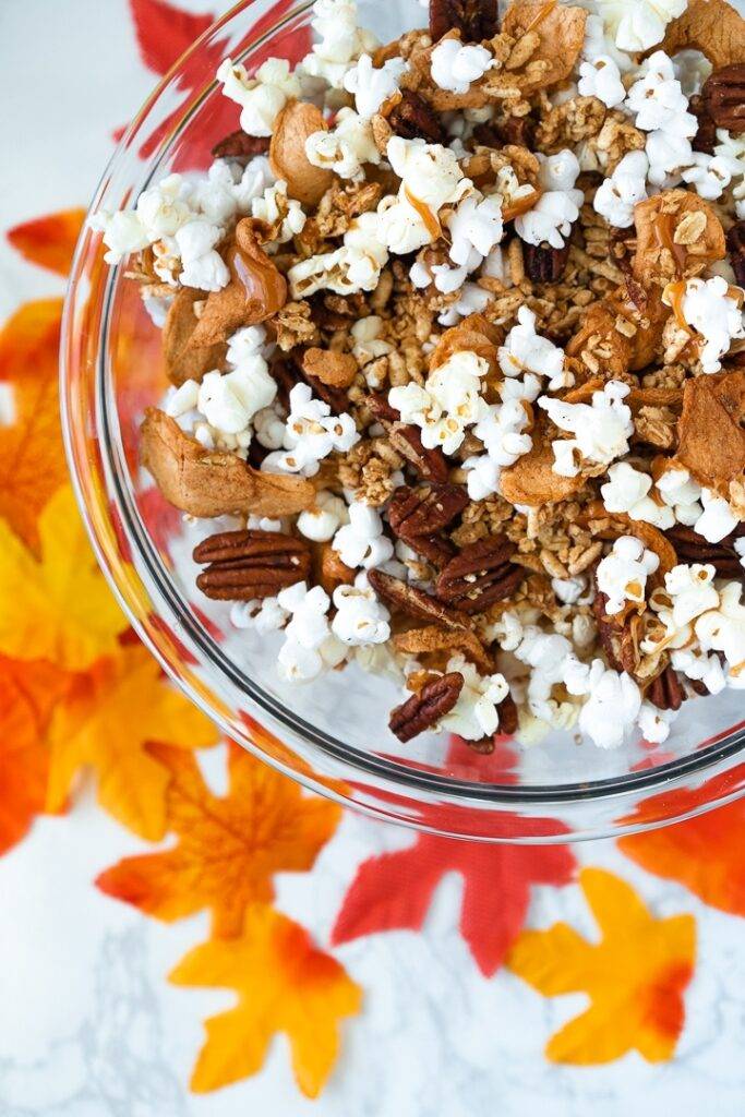 clear bowl with popcorn, pecans, dried apples, and cereal against a white background with fall leaves