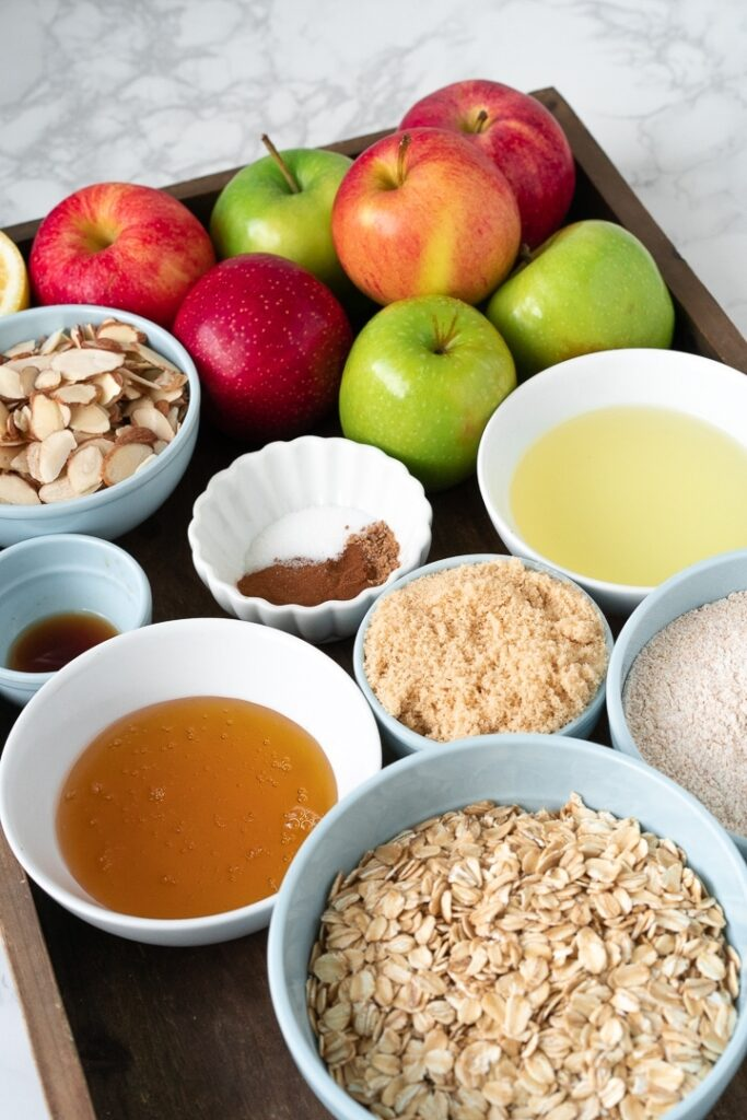 wooden tray filled with bowls of healthy apple crumble ingredients and pile of apples