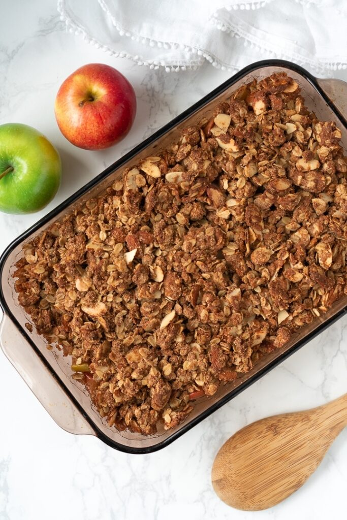 baking dish with baked apple crumble and apples in background