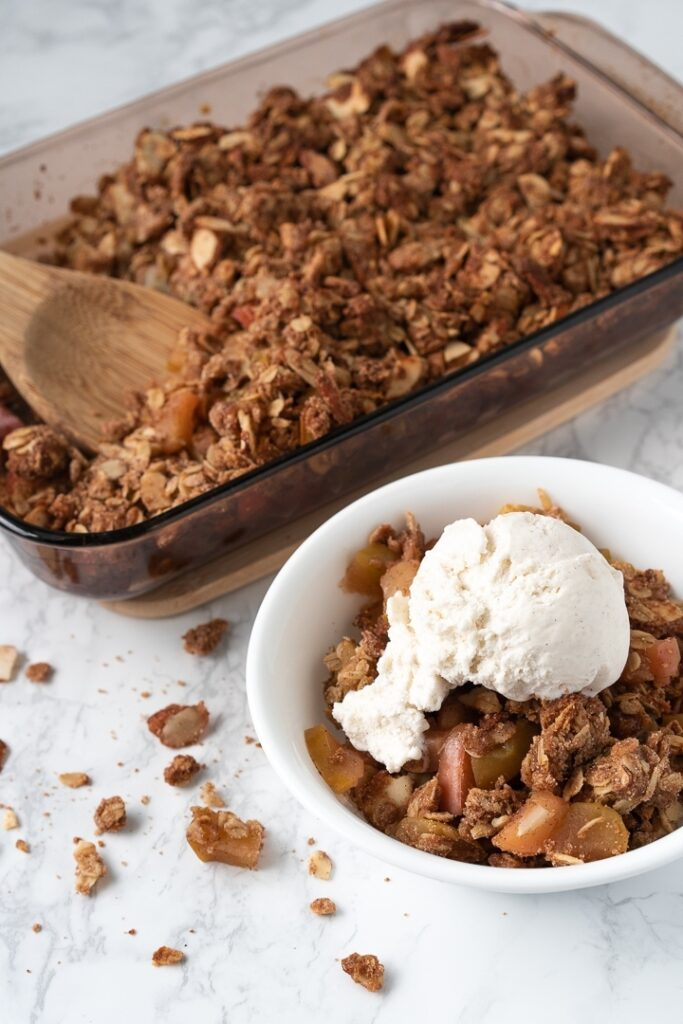 baking dish with apple crumble and white bowl filled with apple crumble topped with ice cream
