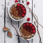 two chocolate smoothie bowls topped with chopped nuts, pomegranate arils, and raspberries