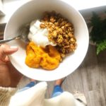 hand holding bowl with yogurt, pumpkin puree, and granola