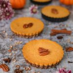three mini pumpkin pies topped with pecans