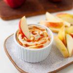 apple slice dipping into cup with caramel dip