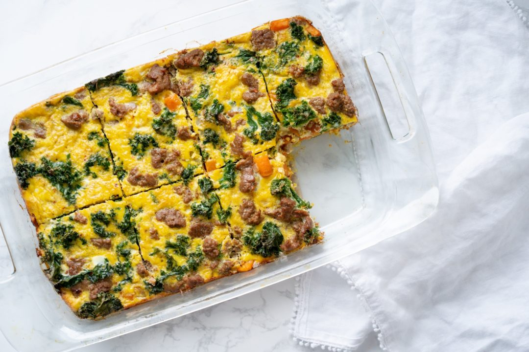 baking dish containing sausage and egg casserole with one piece removed