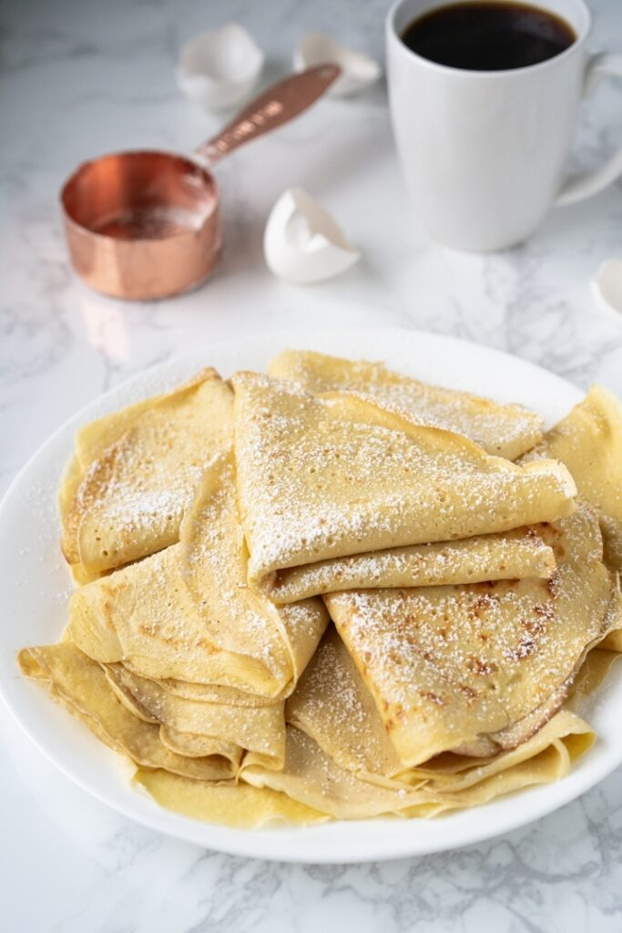 plate of crepes dusted with powdered sugar
