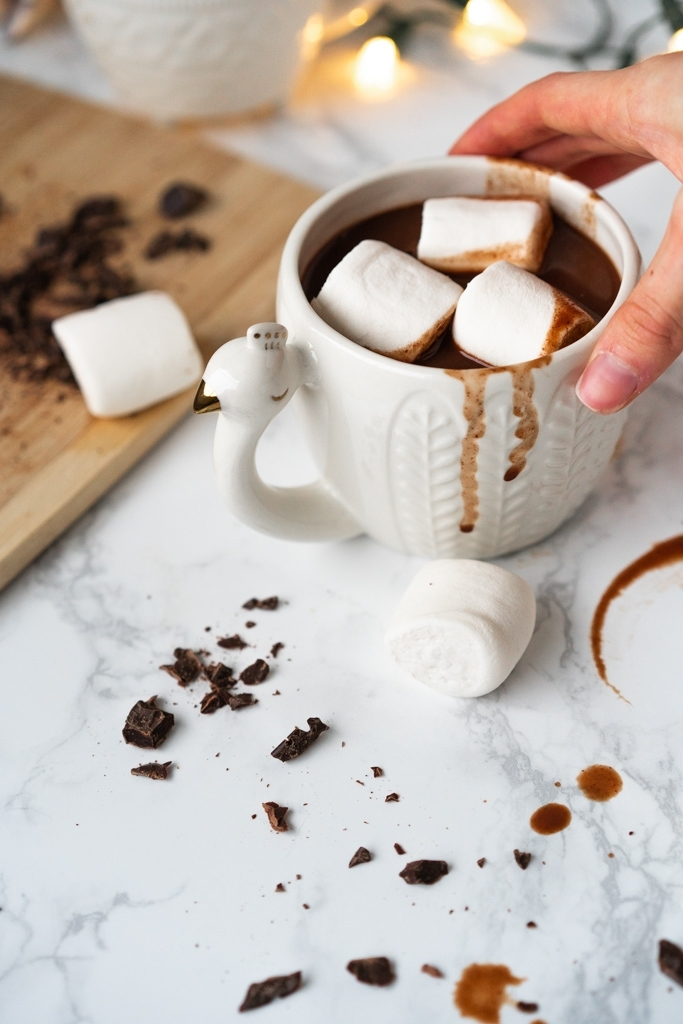 hand holding white mug filled with hot chocolate and marshmallows
