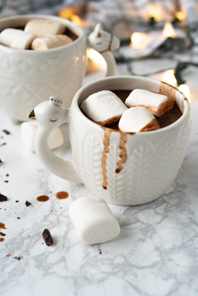 two white mugs filled with hot chocolate and marshmallows