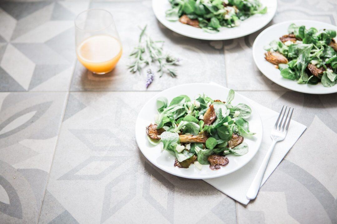 three plates with salad sitting on tile floor